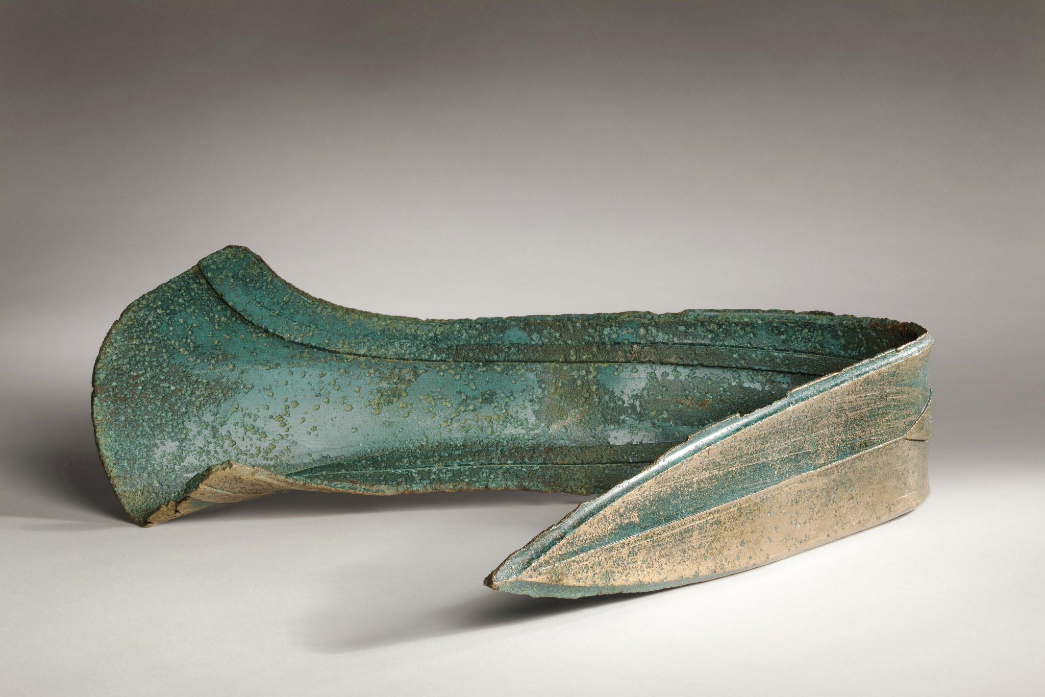 a photo of a bent dagger with green verdigris