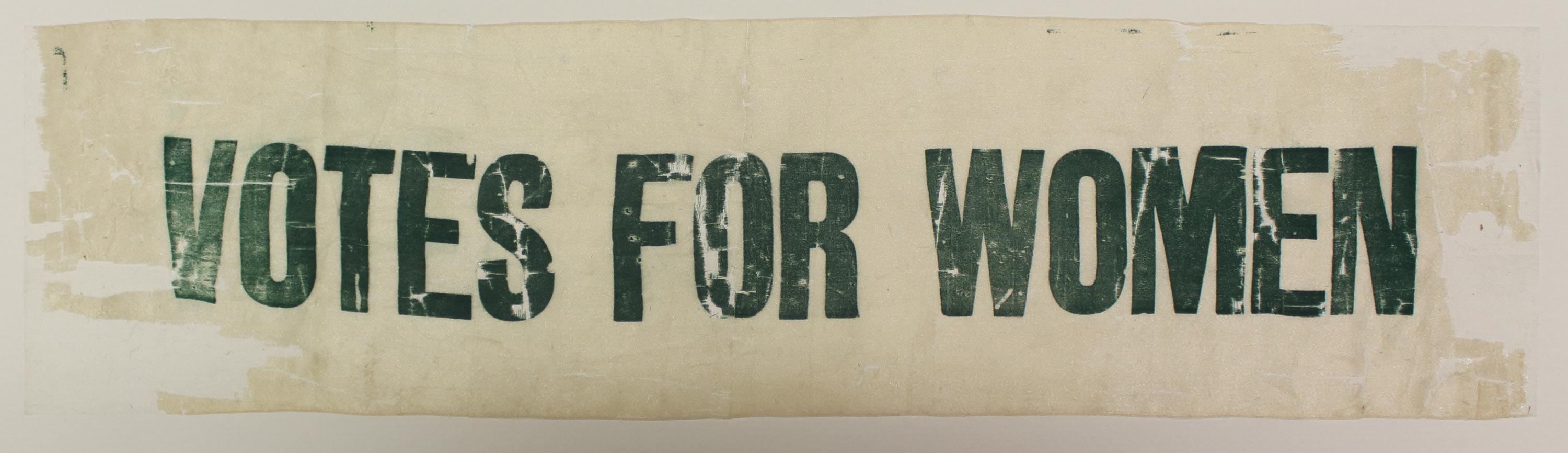 a photo of a piece of cream fabric with votes for women printed in green across it