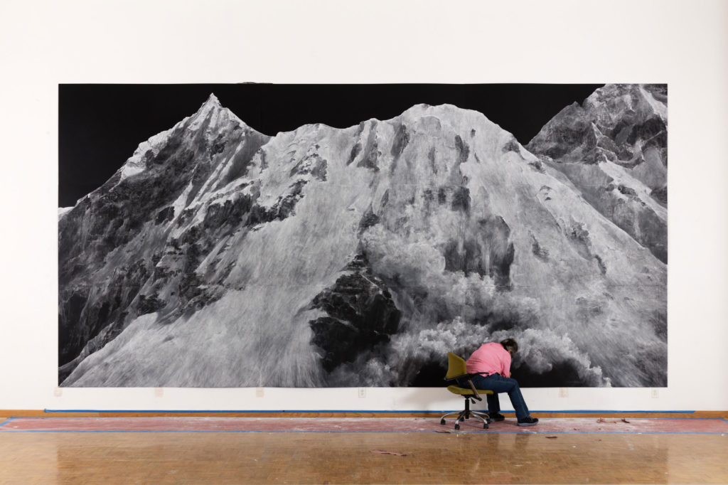 photograph of artist working on large-scale chalk drawing of mountain on gallery wall