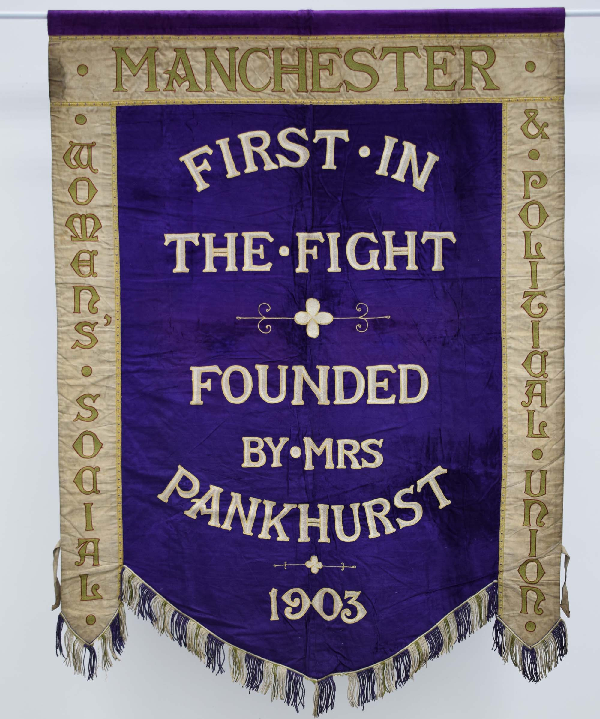 a purple banner with the words first in the figt founded by Mrs Pankhurst 1903