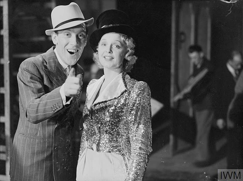 a film still of man in a trilby and suit with a woman in a top hat and sparkly short tunic