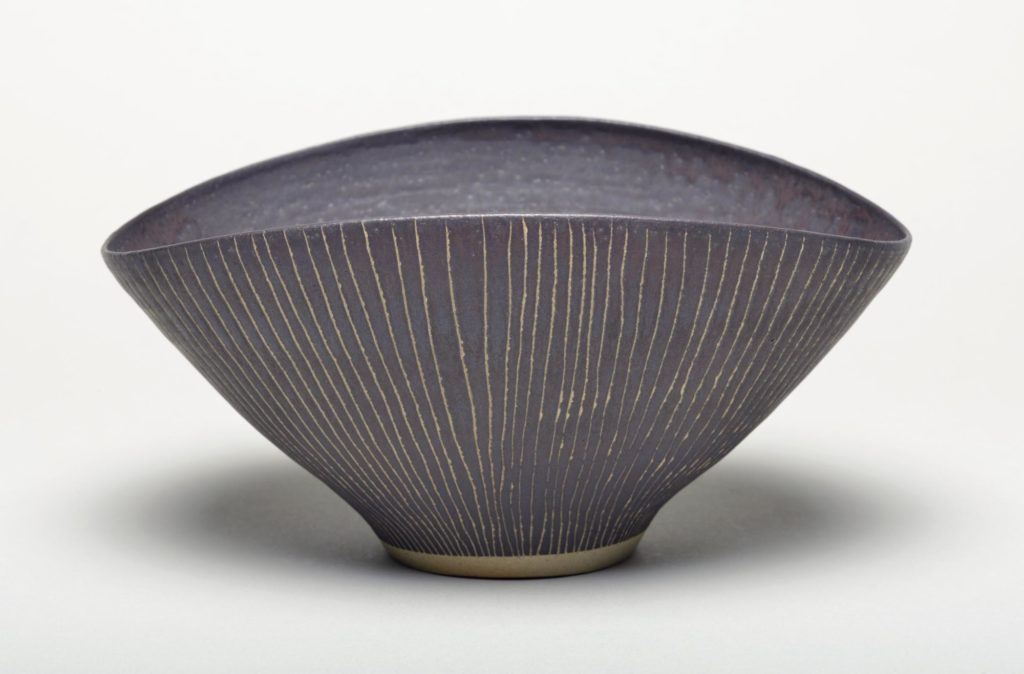Small stoneware footed bowl, with oval rim. Matt brown/black. . Vertical lines are scribed through the glaze on the outside.