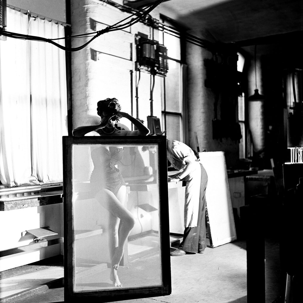 photograph of woman in swimsuit standing behind a translucent screen in a warehouse