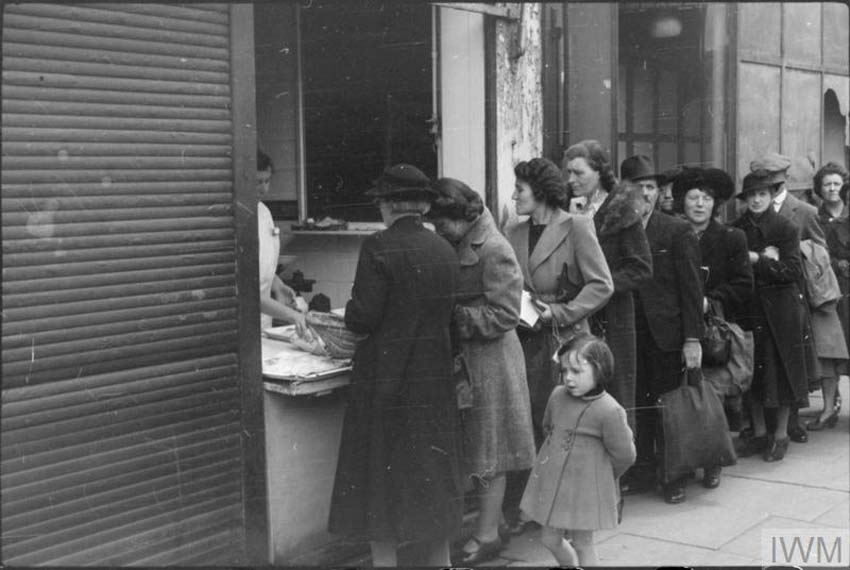 a black and white photo of women queuing outside a fishmongers