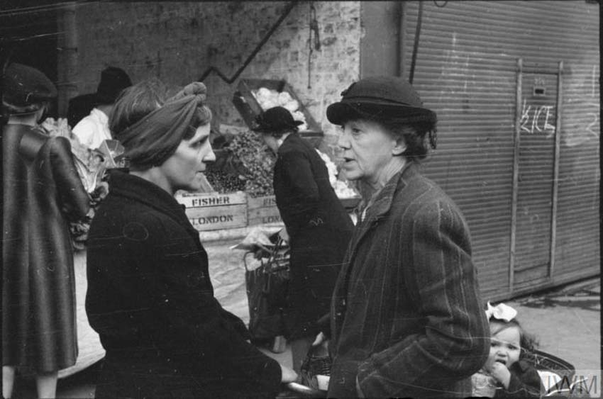 a photo of two women talking in a street next to a shuttered market stall