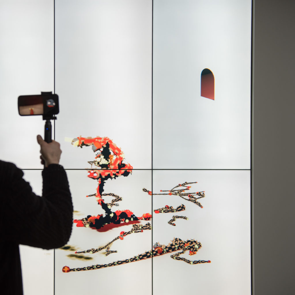photograph of installation view of interactive simulation exhibition, showing person holding device at a screen