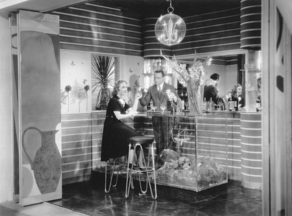 black and white photograph of man and woman at a glass bar with diorama inside. The room has wood panelled walls and glass shelves holding spirit bottles and cocktail equipment