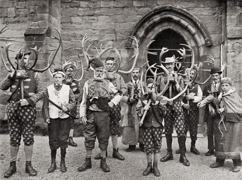 a black and wite photo of a group of men and boys dressed strangely with deer antlers