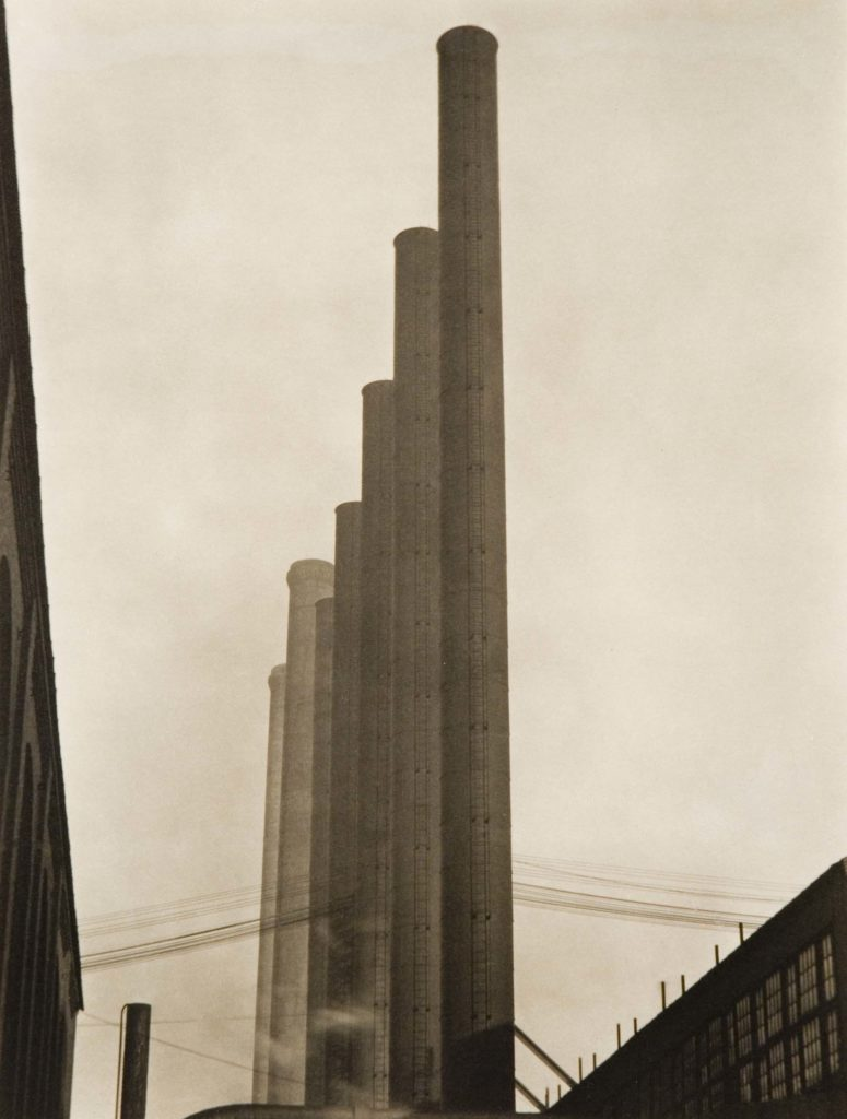 a black and white photo of a large series of industrial towers