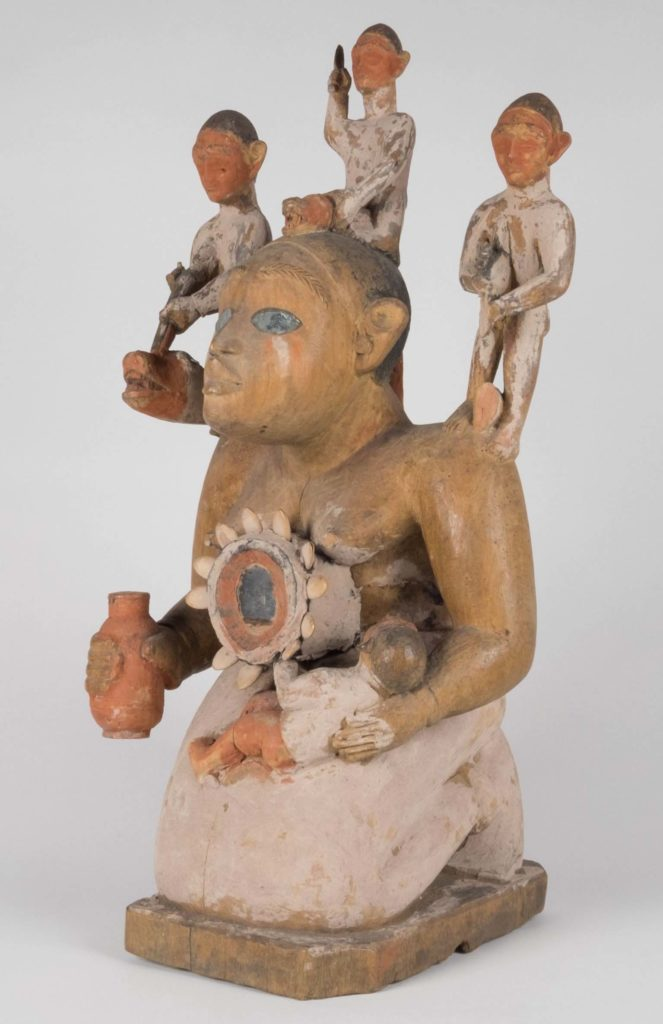 a carving of a female figure with various other figures standing on its shoulders