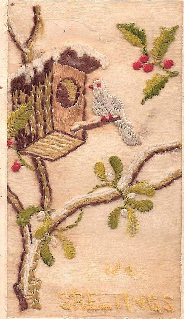 an embroidered Christmas card with a birds house in a tree covered in snow