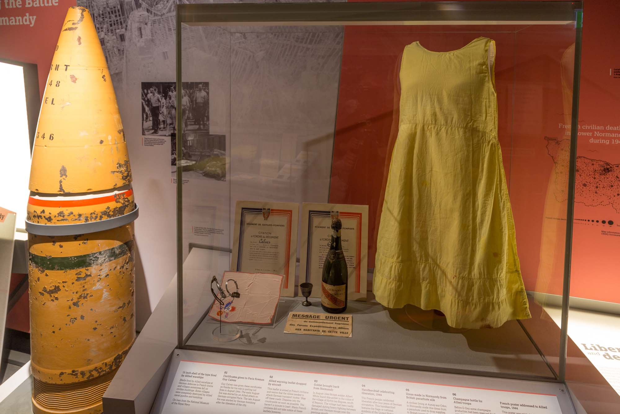 a photo of a yellow silk dress in a display case
