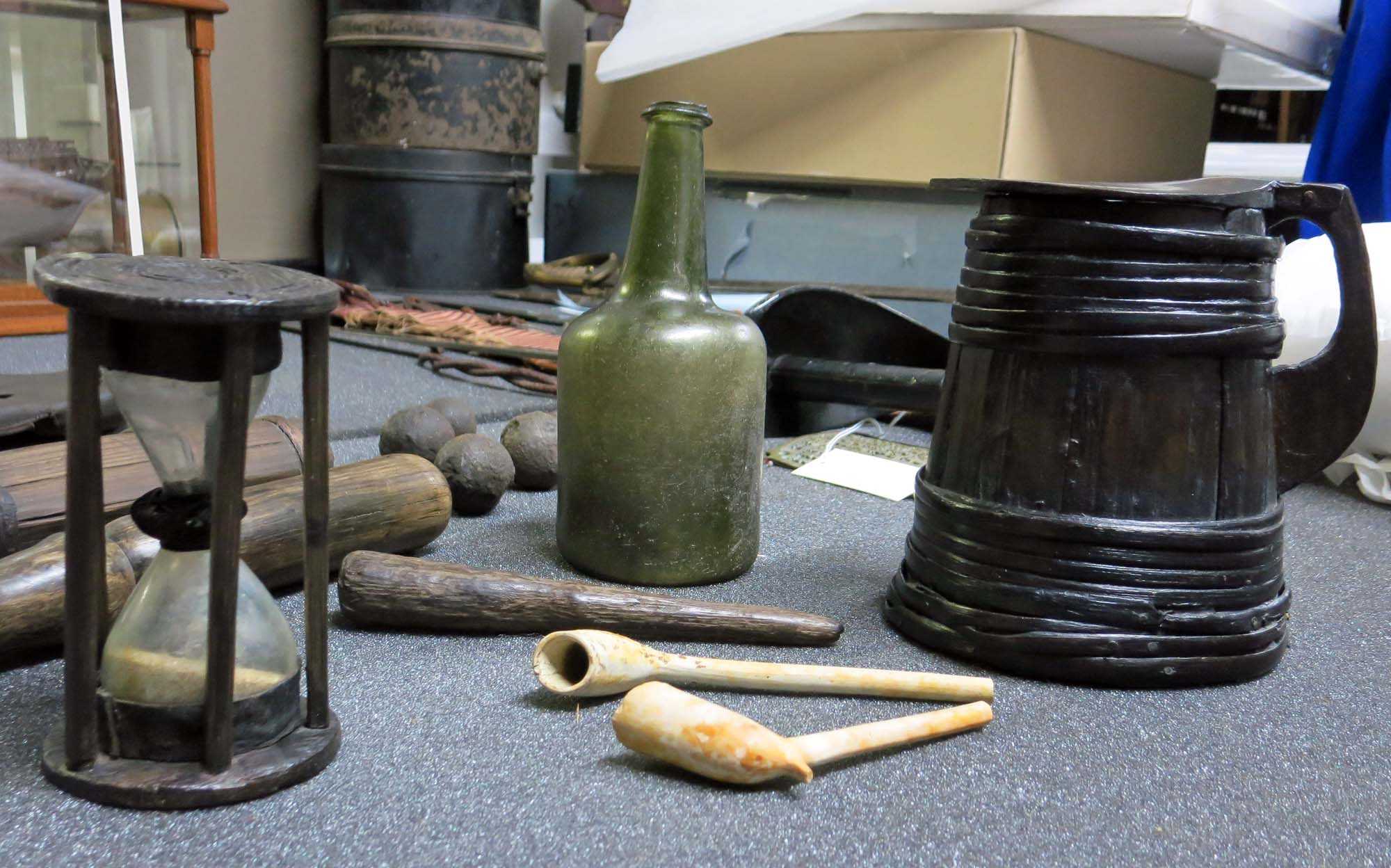 a photo of a tankard, clay pipes, hourglass and other objects on a table