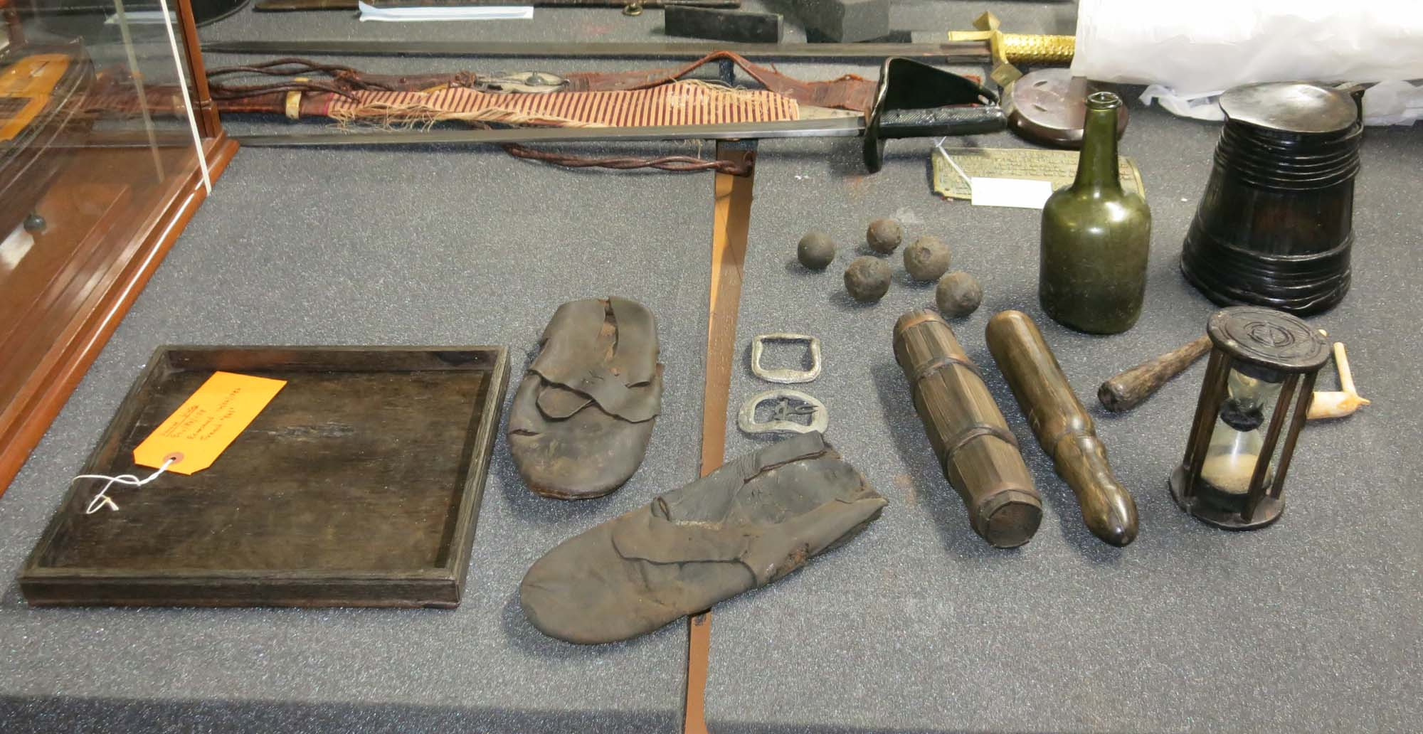 a photo of various artefatcs including a green glass bottle pegs, a shoe, hour glass and grape shot on a table