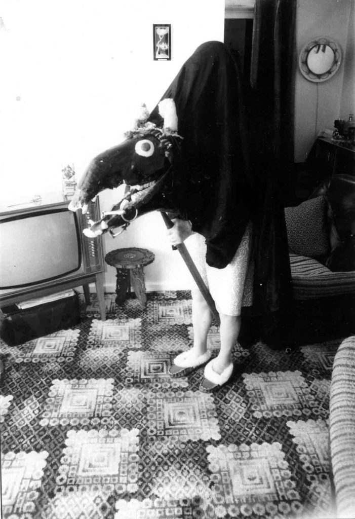 a black and white photo of woman with a hood and horse head hobby horse outfit in her front room