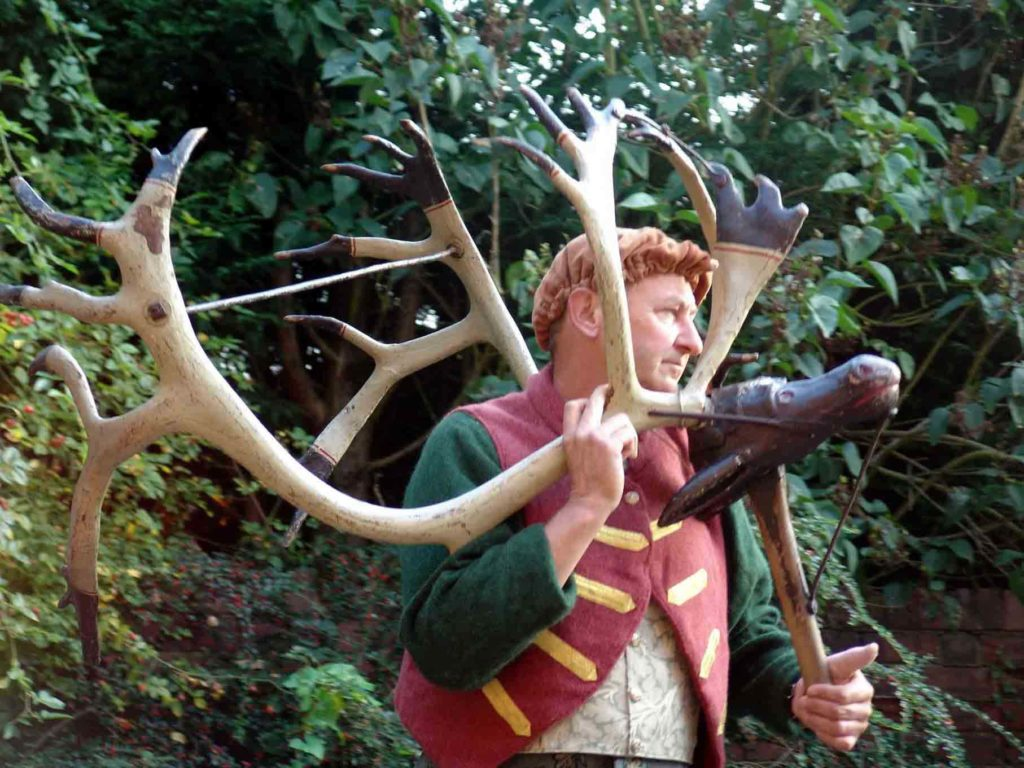 a colour photo of a man wearing a scarlet tunic and holding a pair of antlers