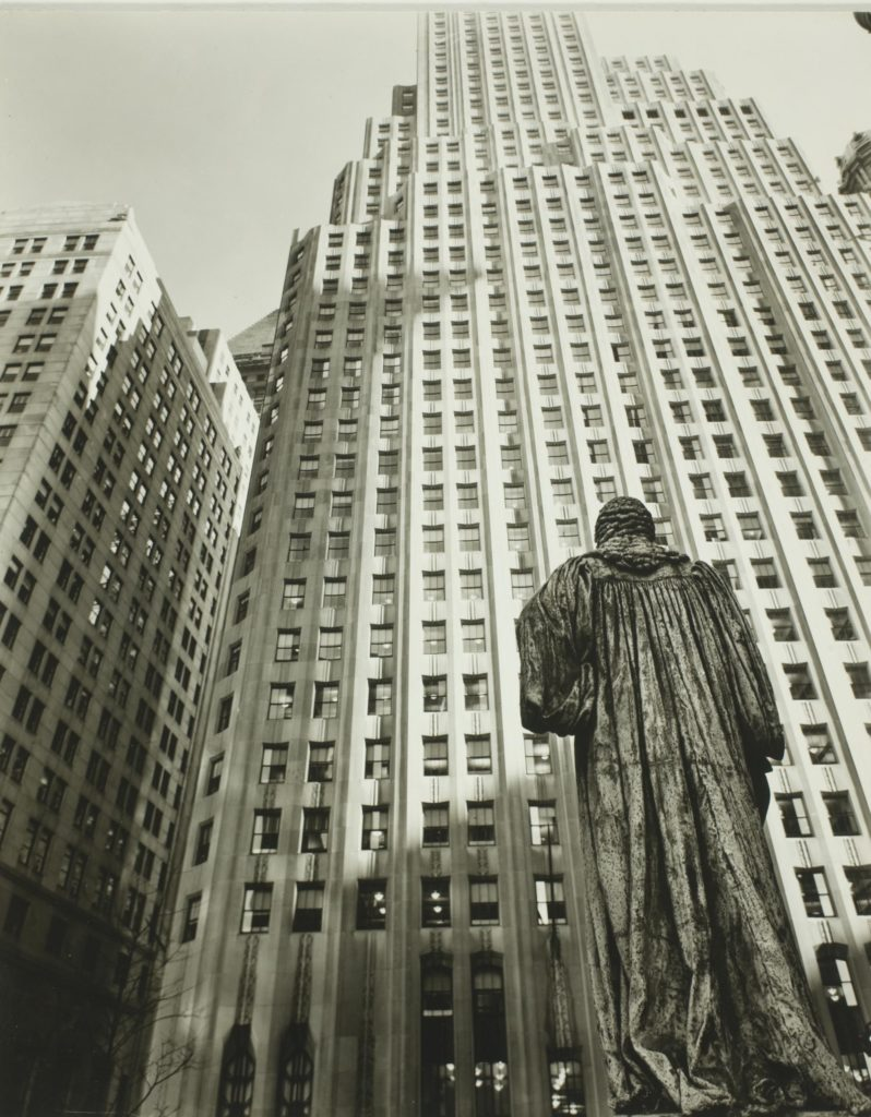 a photograph of a US skyscraper with a statue in the foreground