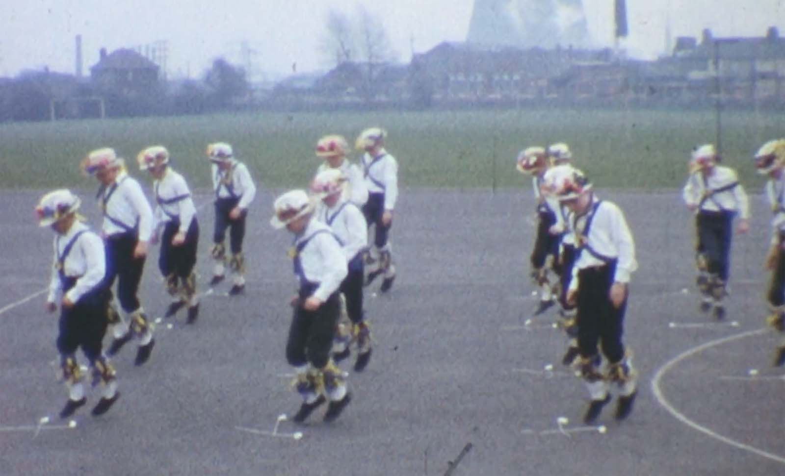 a filsm still showing Morris Men dancing on a playground in a city park