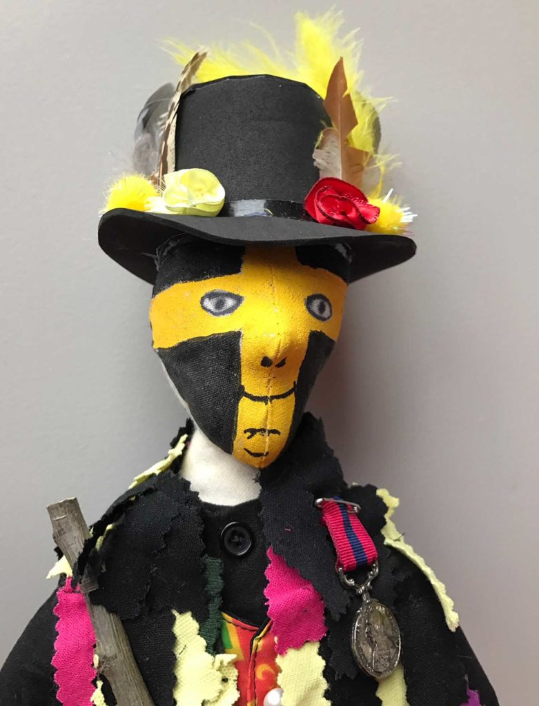 a photo of a doll with a black top hat and yellow and black and yellow stars