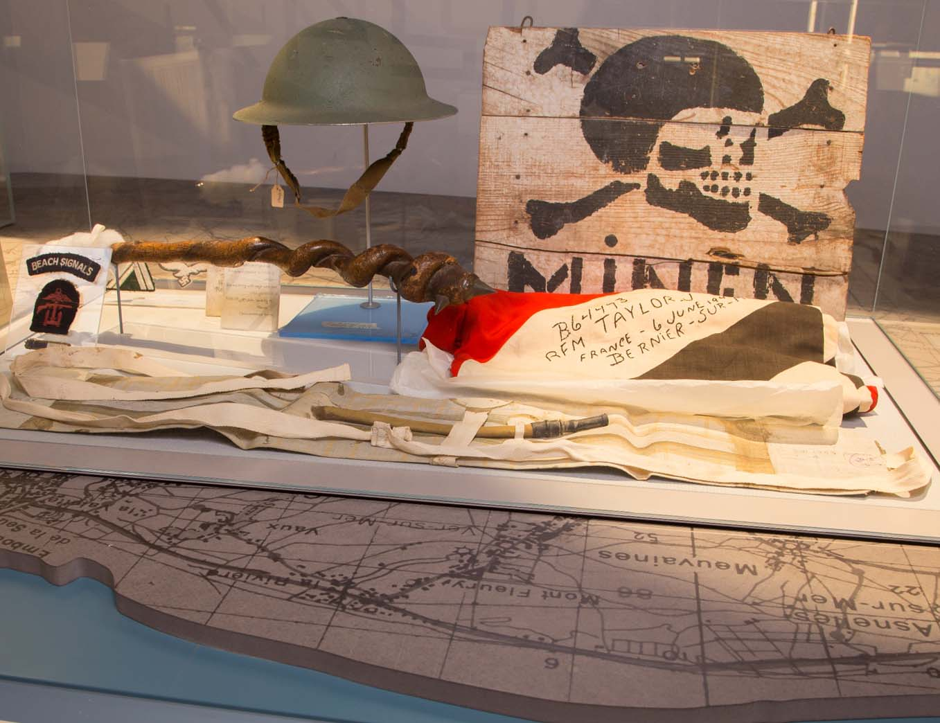a photo of a display case with a German mine field sign and a British helmet