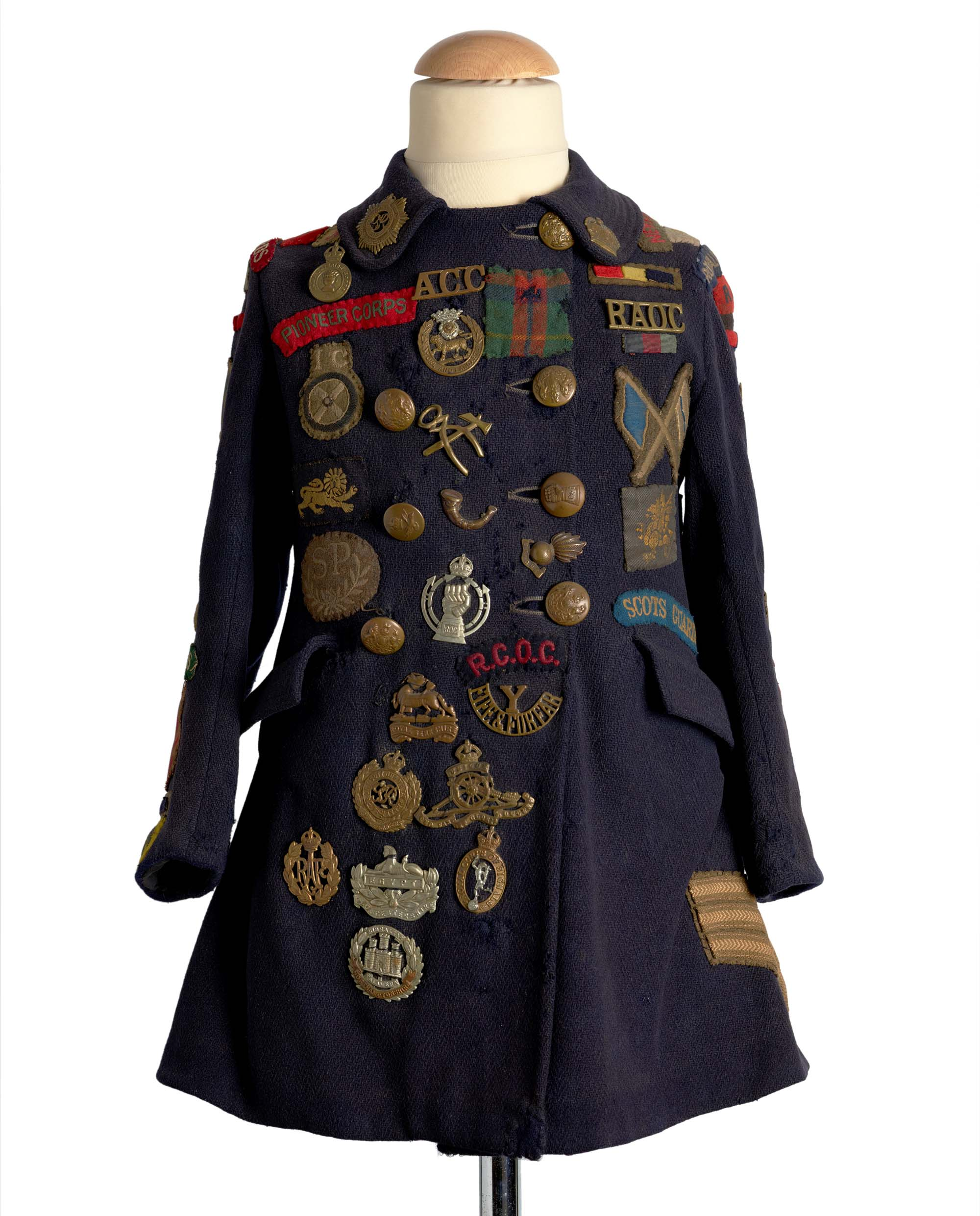 a photo of a blue girls coat covered with military brass and cloth badges