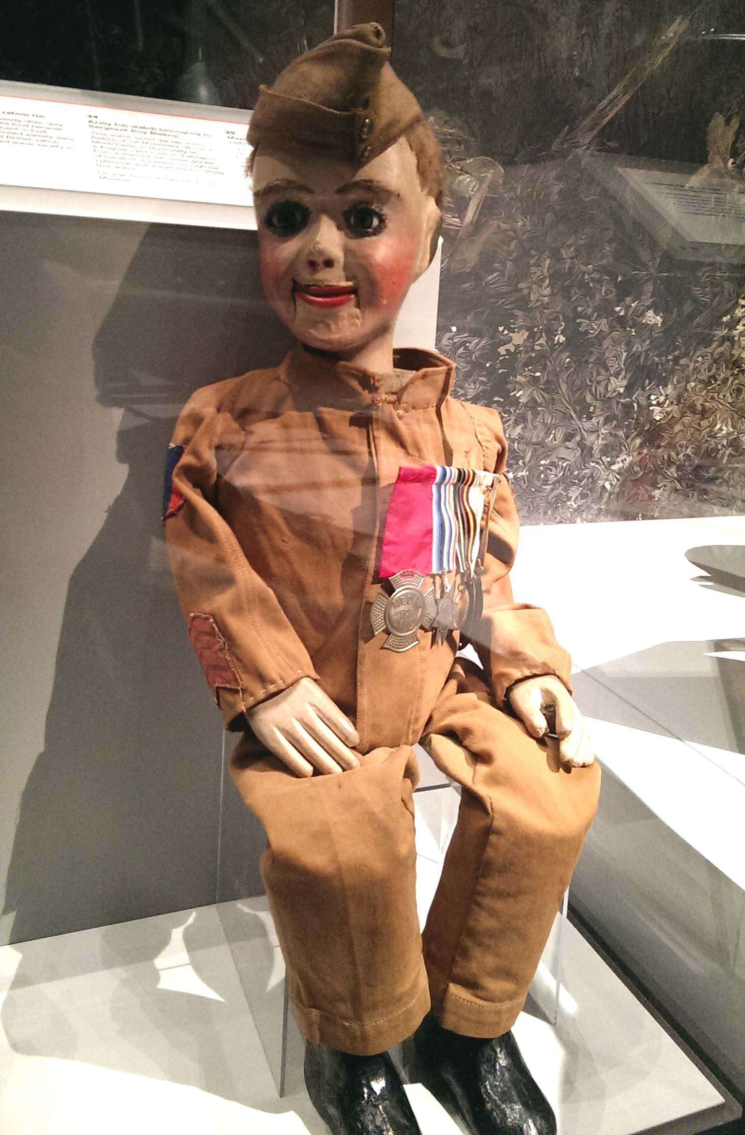 a photo of a ventriloquists dummy dressed as a soldier with cap and medals in a display case at the D-Day Story Museum