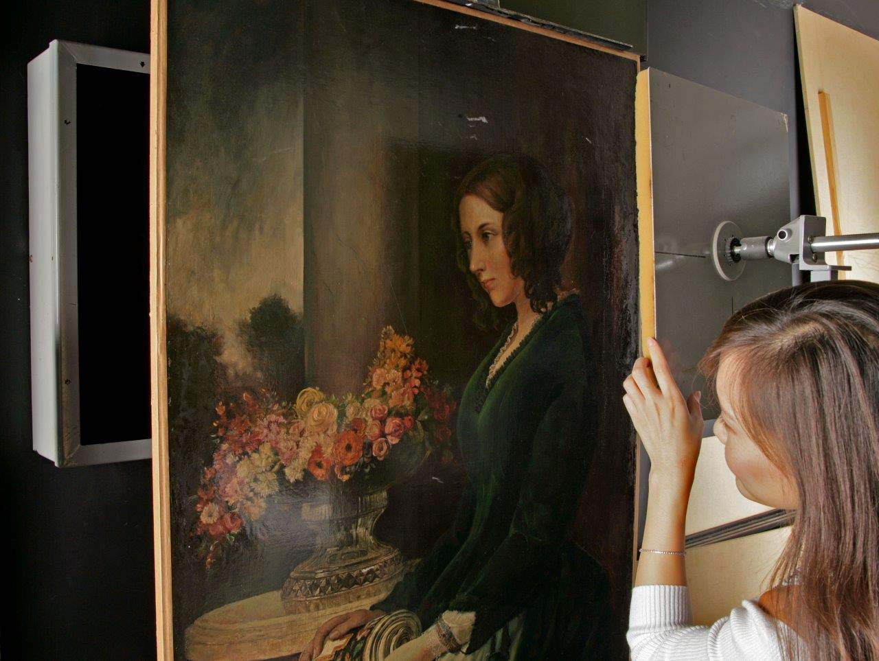 a photo of a womna using a kind of X-ray machine next to portrait of woman in a green dress