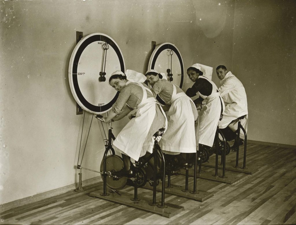 a photo of three female and one male nurse on exercise bikes