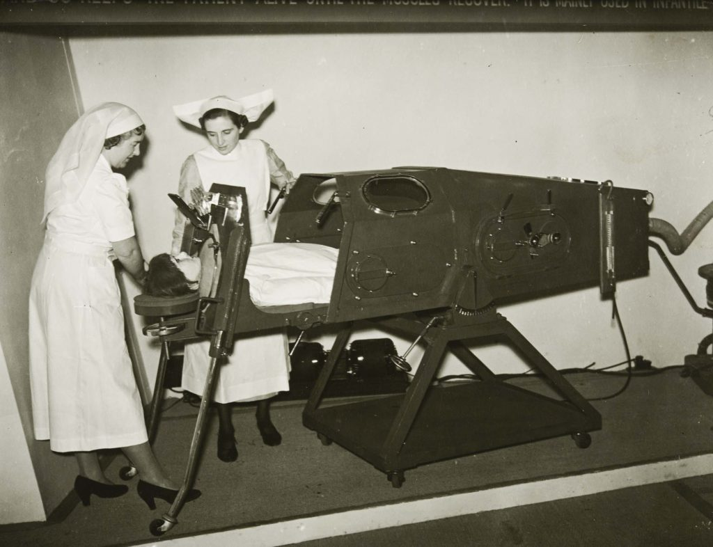 a photo of two nurses using an iron lung with a mannequin lying prone within the contraption
