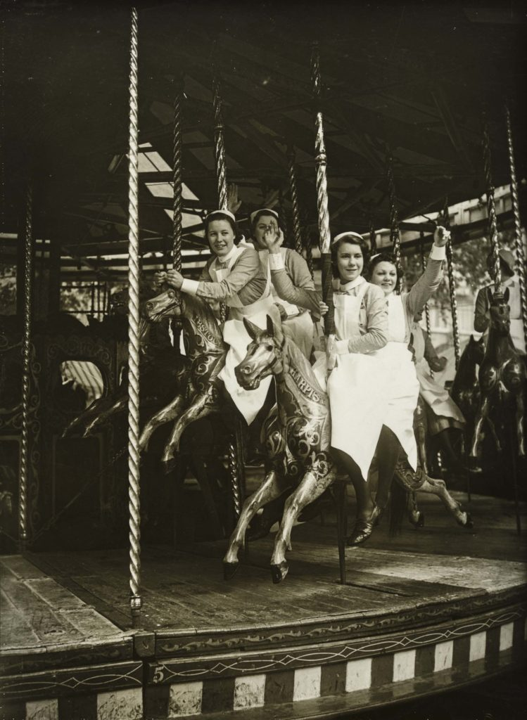 a black and white photo of nurses in uniform on a merry go round