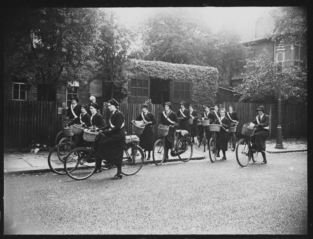 a black and white photo of a large group of midwives on bicycles