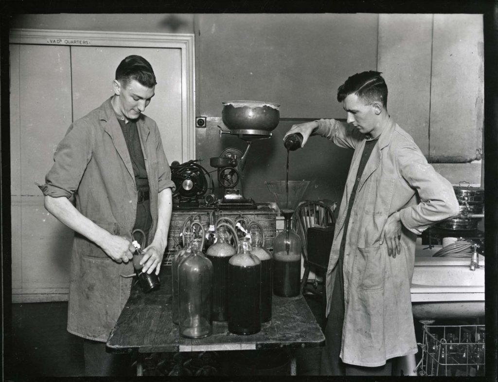 a photo of two men filling glass jars with blood