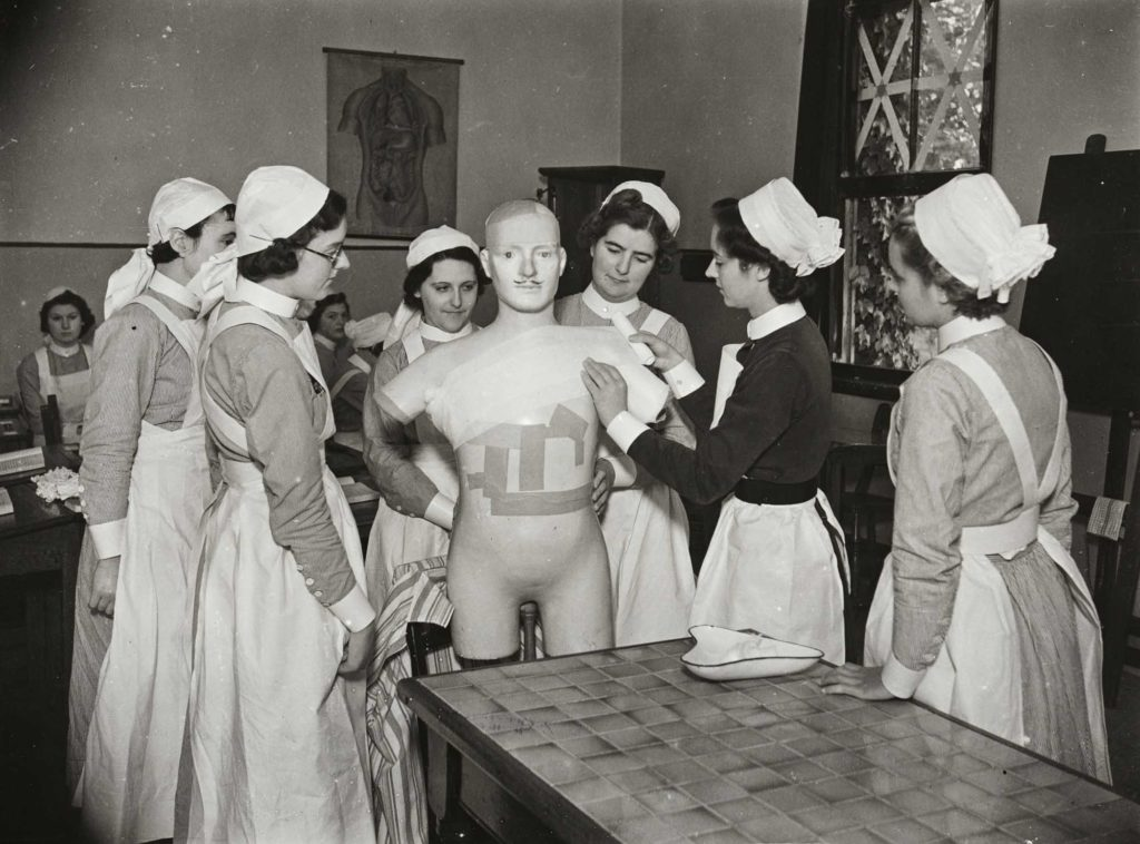 a photo of a group of nurses grouped around a mannequin