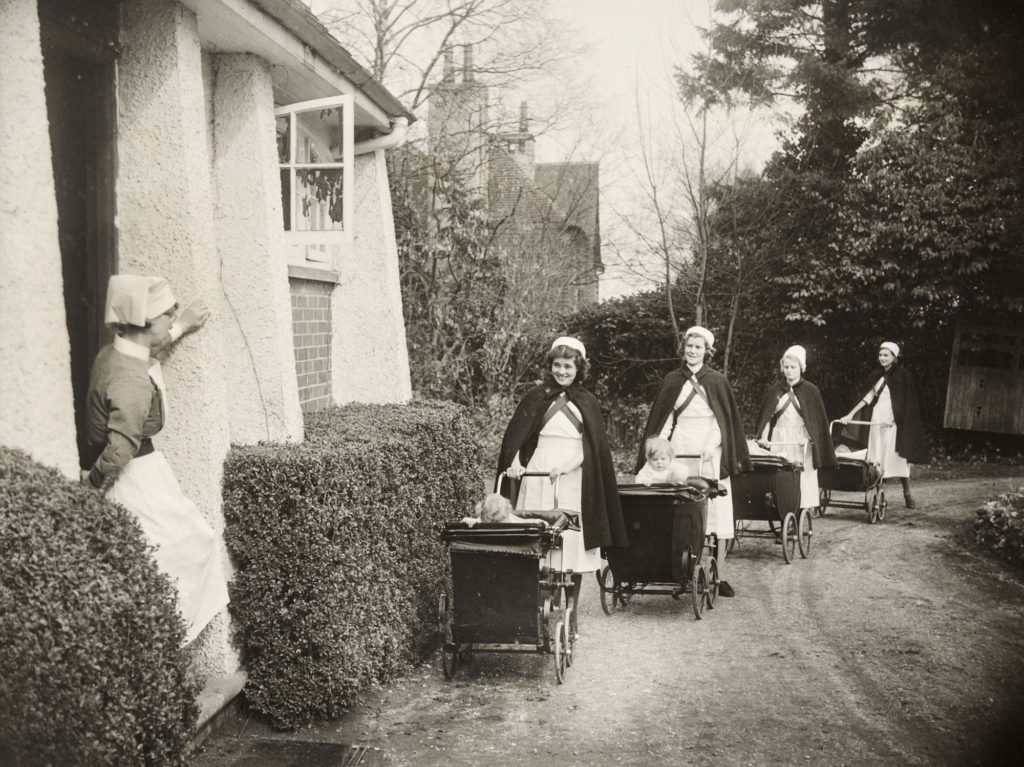 a black and white photo of nurses pushing prams up a driveway toward a house