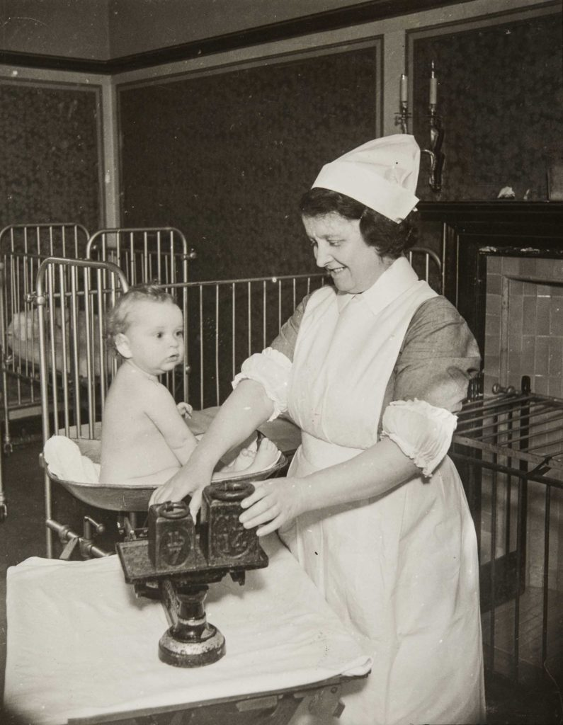 a photo of a nurse with a baby sat in a large weighing scale