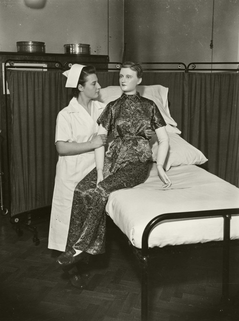 a photo of a nurse with a female mannequin in a dressing gown propped up in a bed