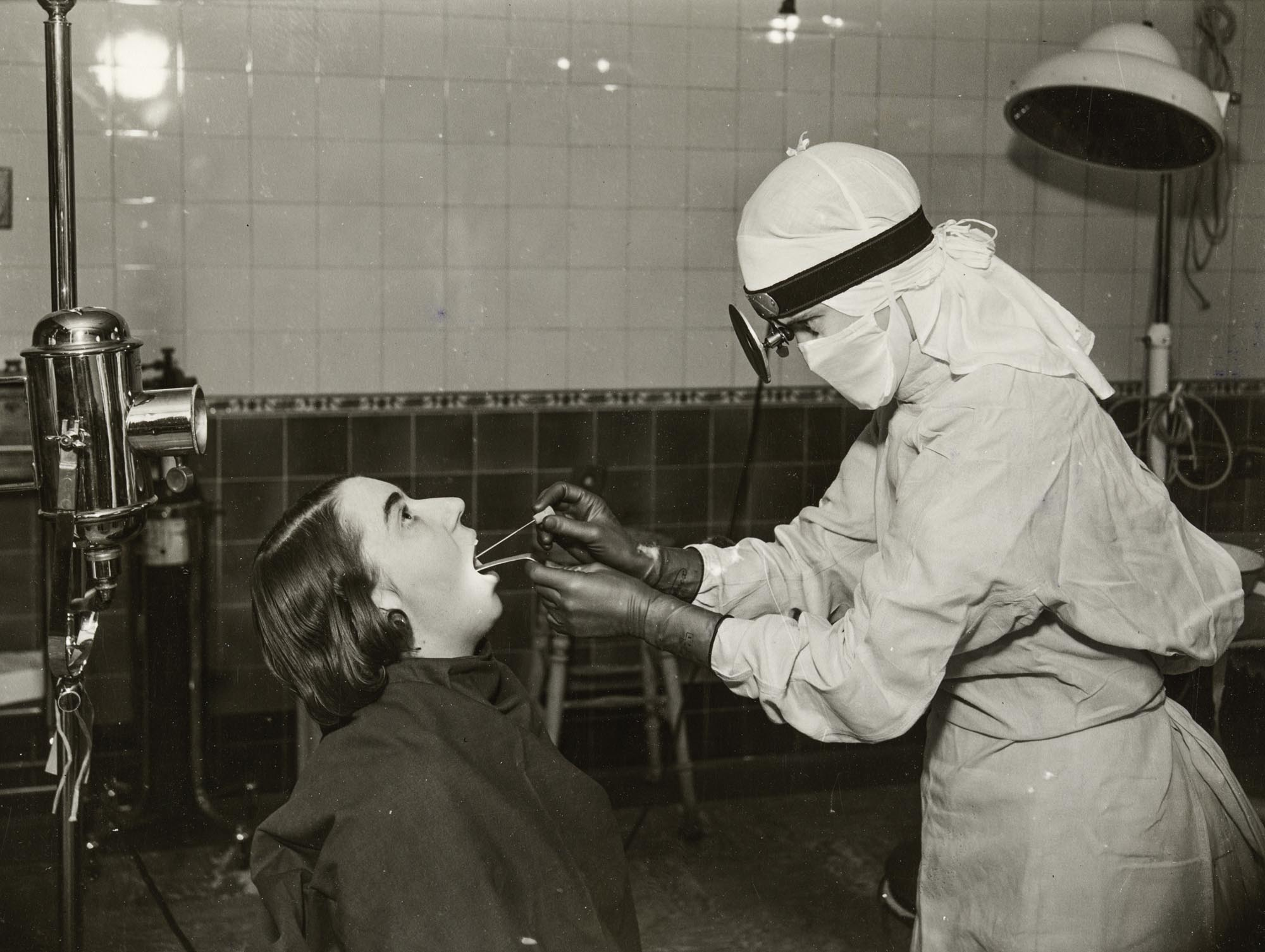 a black and white photo of a figure in white gown taking a swab from an open-mouthed woman