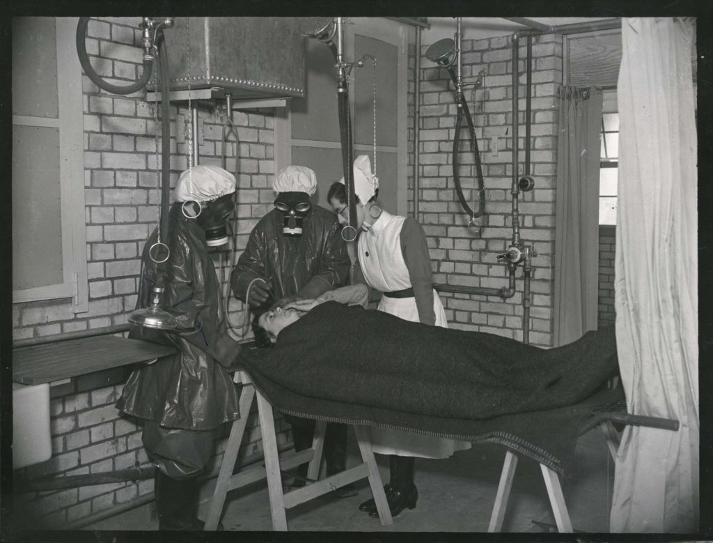 a photo of nurses in gas masks attending a person a bed