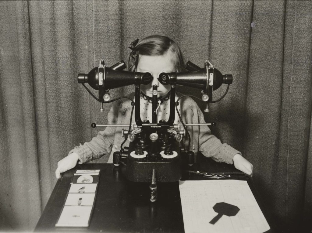 a girl seated with opthalmic devices fitted to her eyes