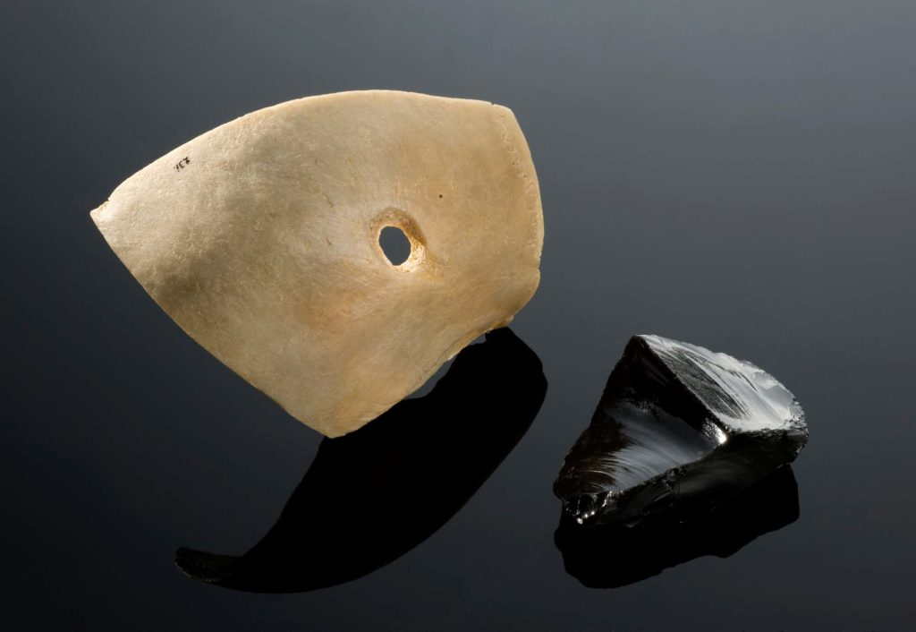 a photo of a skull fragment with a hole in it with a sharp piece of black obsidian volcanic rock