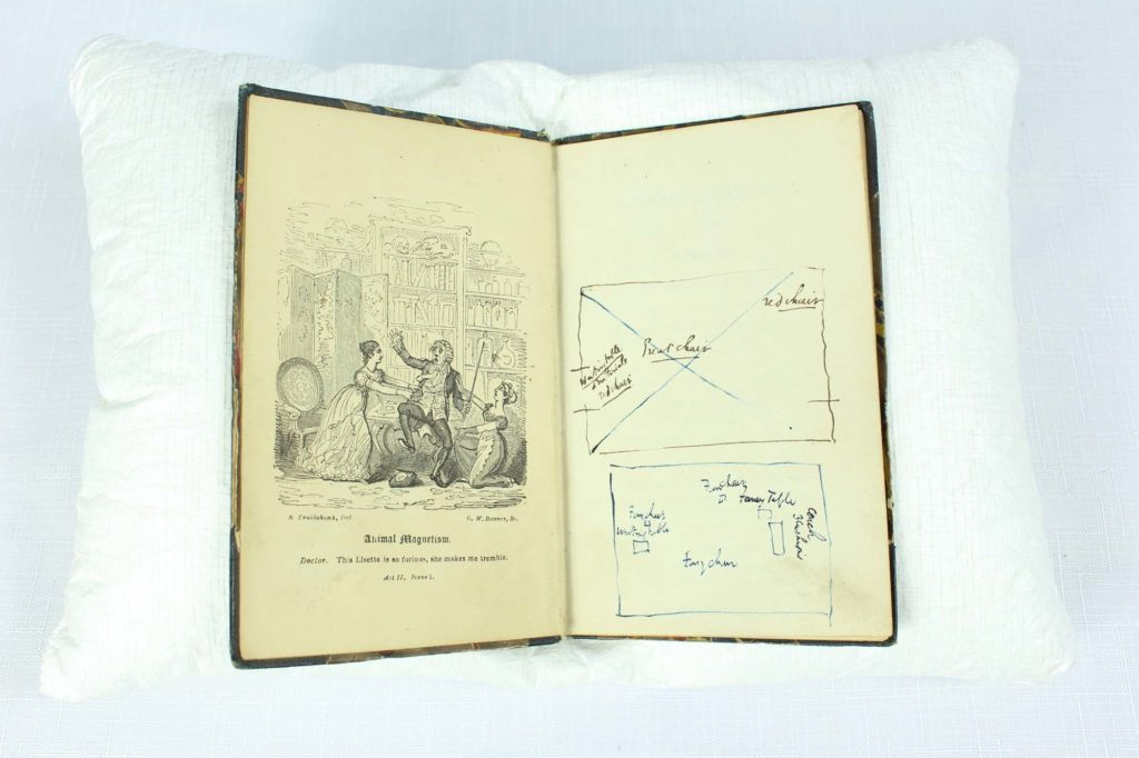 a photo of an open book with frontispiece illustration and annotations