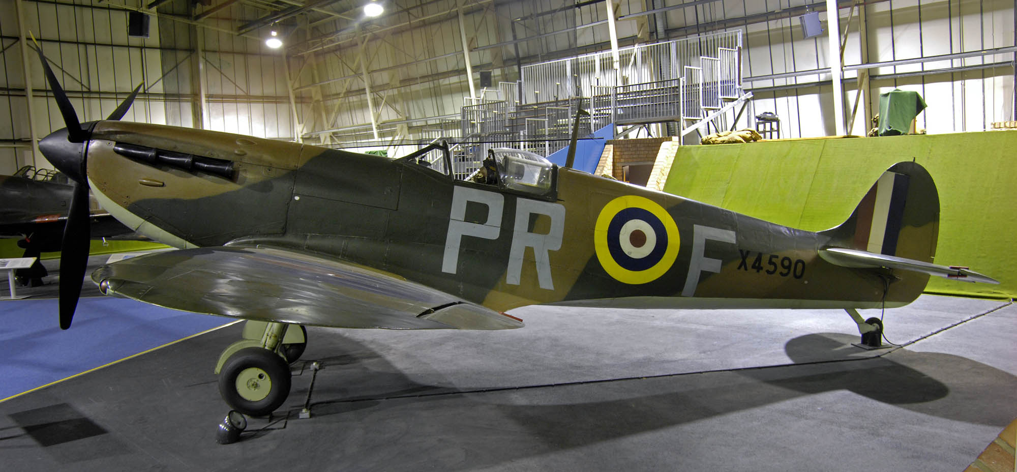 a photo of an RAF Spitfire in Brown and white camouflage in a museum hangar