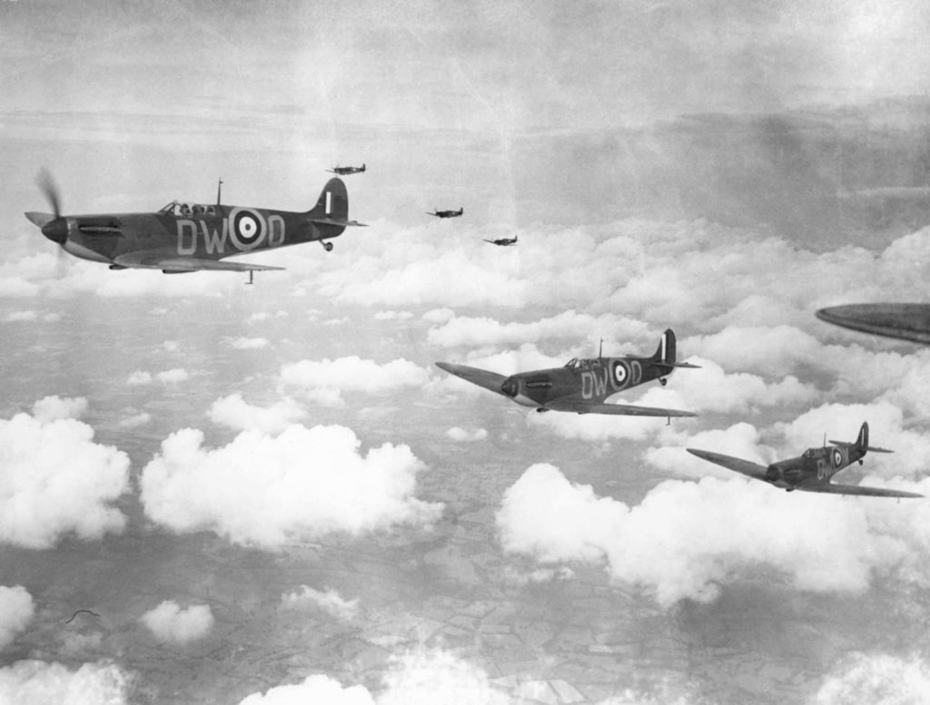 a black and white photo of Spitfire flying in formation above the clouds