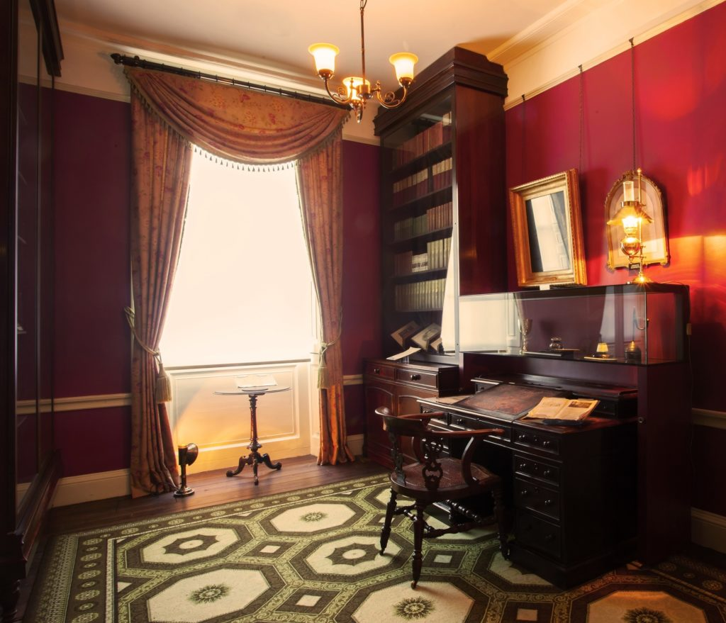 a photo of a Victorian era interiror with desk and bookshelves leaning against a red wall