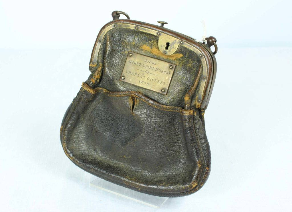 a photo of a leather purse like bag with a metal plaque on it