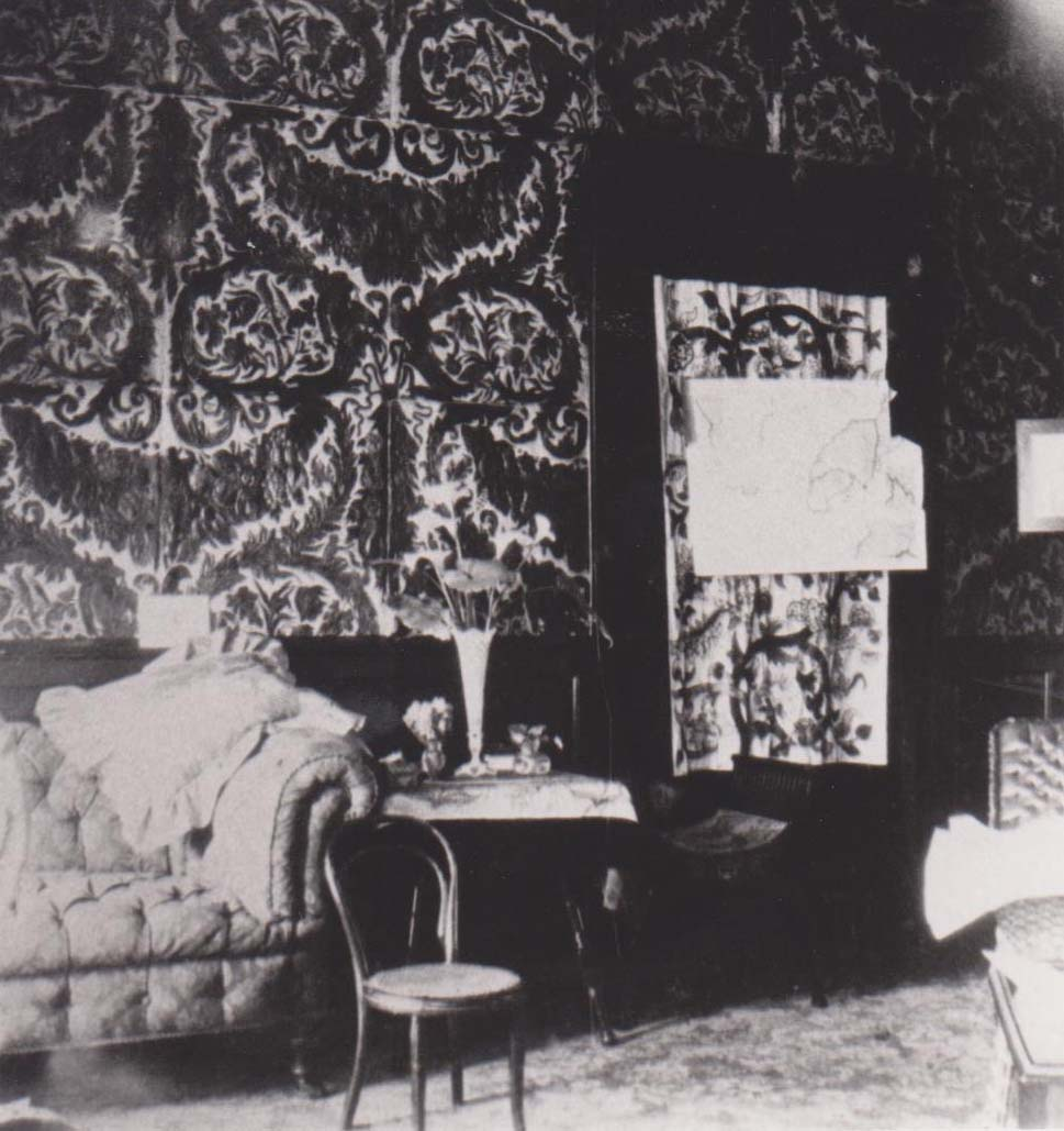 a black and white photo of a room with chaise longes and heavy wallpaper