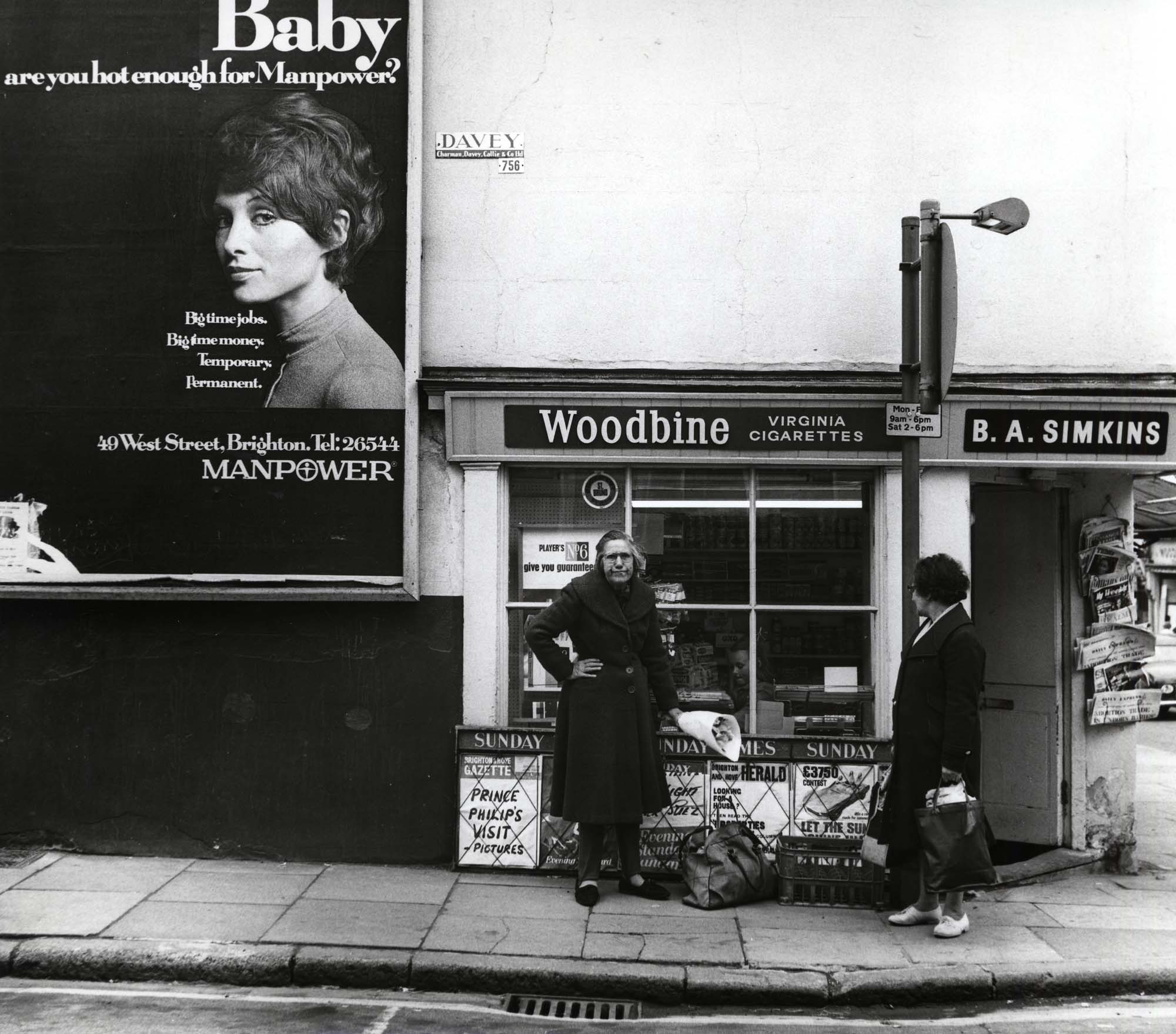 a photo of two elderly ladies on a street outside a shop beneath a hording with a young model featured on it