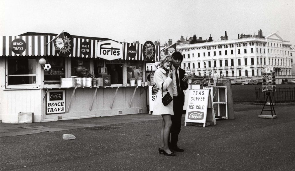 a photo of a young couple with ice creams walking away from a seafront kiosk