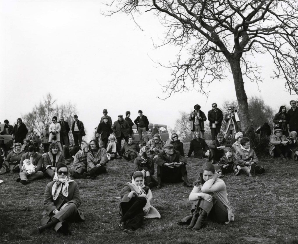 a photo of various country folk wrapped against the elements at a point to point race