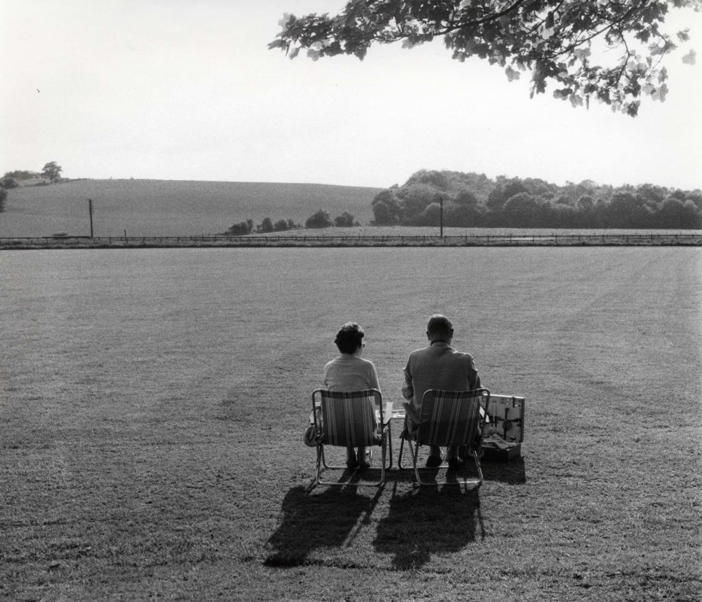 a photo of a couple picnicking with deckchairs in a mown field